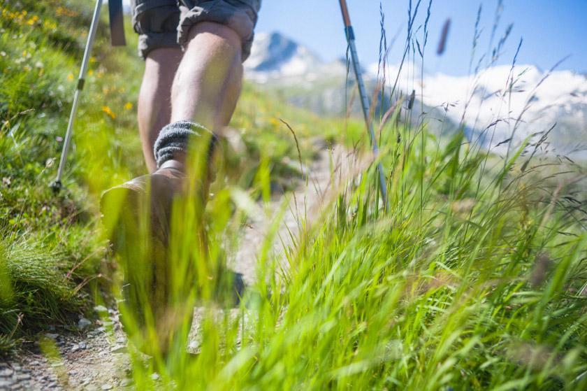 Ein Wanderer geht einen Bergweg entlang. Im Fokus sind seine Wanderschuhe. Sie sind knöchelhoch und aus braunem Wildleder.