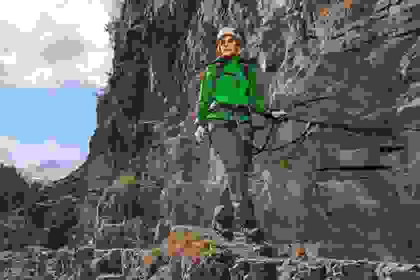 Eine Frau geht in Bergstiefeln und grüner Softshelljacke einen schmalen Gebirgspass entlang.