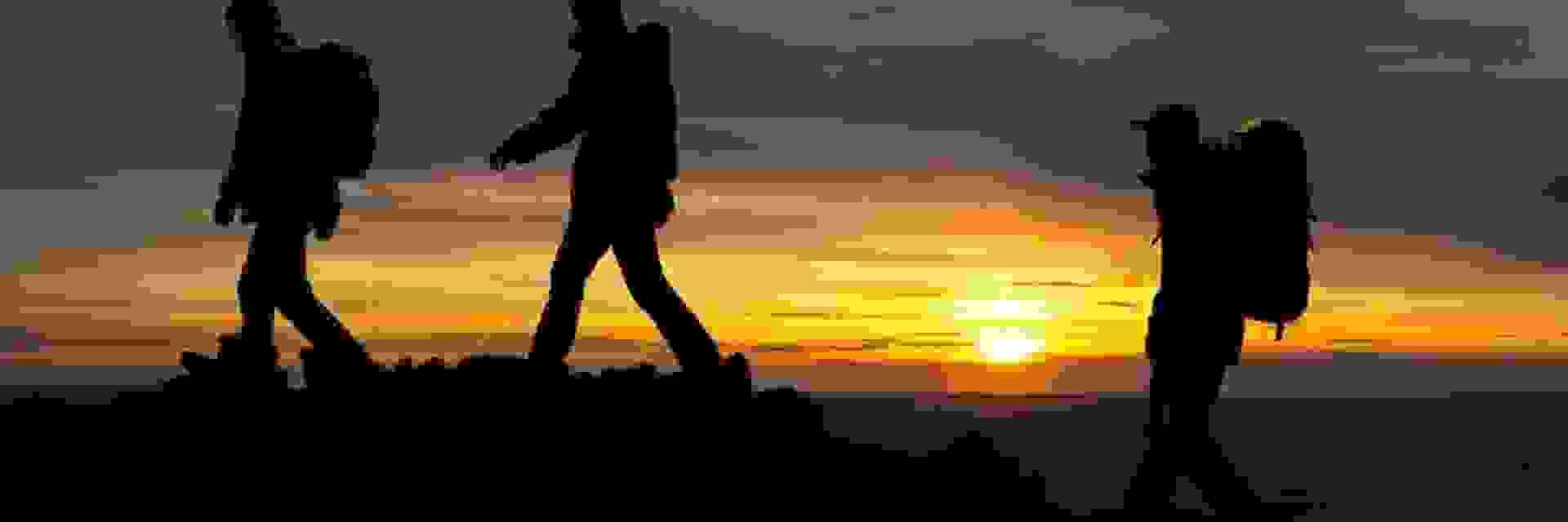 3 Wanderer in der Nacht unterwegs in einem Gebirge. Im Hintergrund ist ein Sonnenuntergang zu sehen.