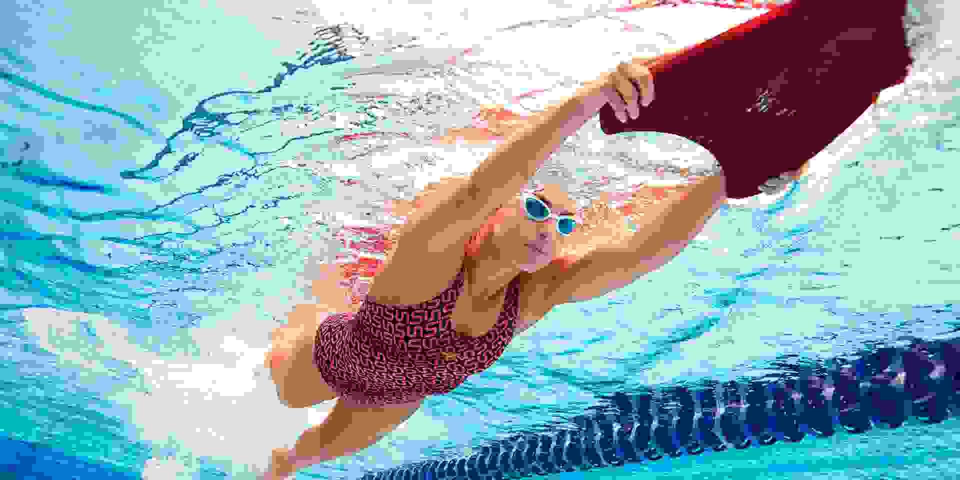 Eine Frau übt Beintechnik beim Schwimmen mit einem Schwimmbrett