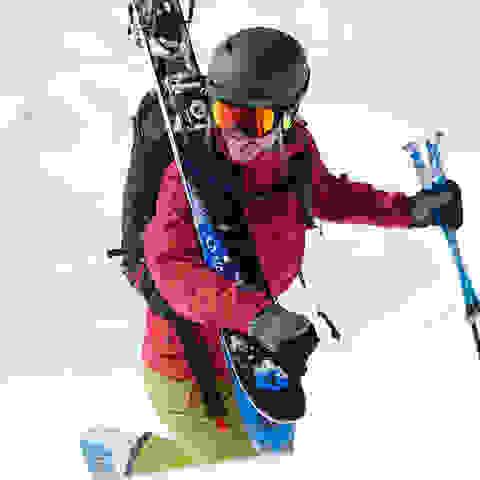 Eine Skifahrerin geht mit ihren Ski auf der Schulter und Skistöcken in der Hand ein Stück die Piste hinauf