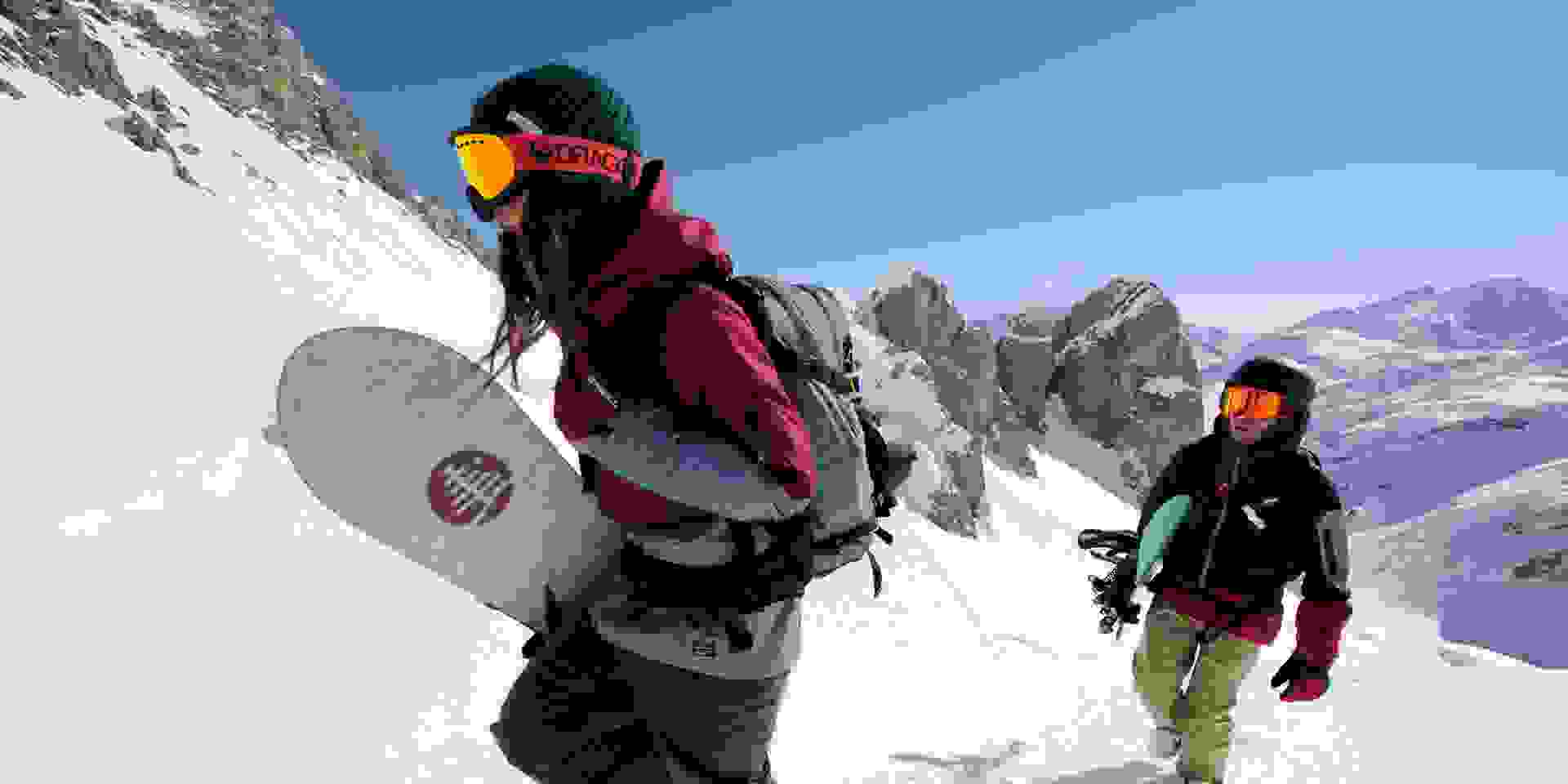 Zwei Snowboarder steigen einen unberührten Tiefschneehang hinauf.