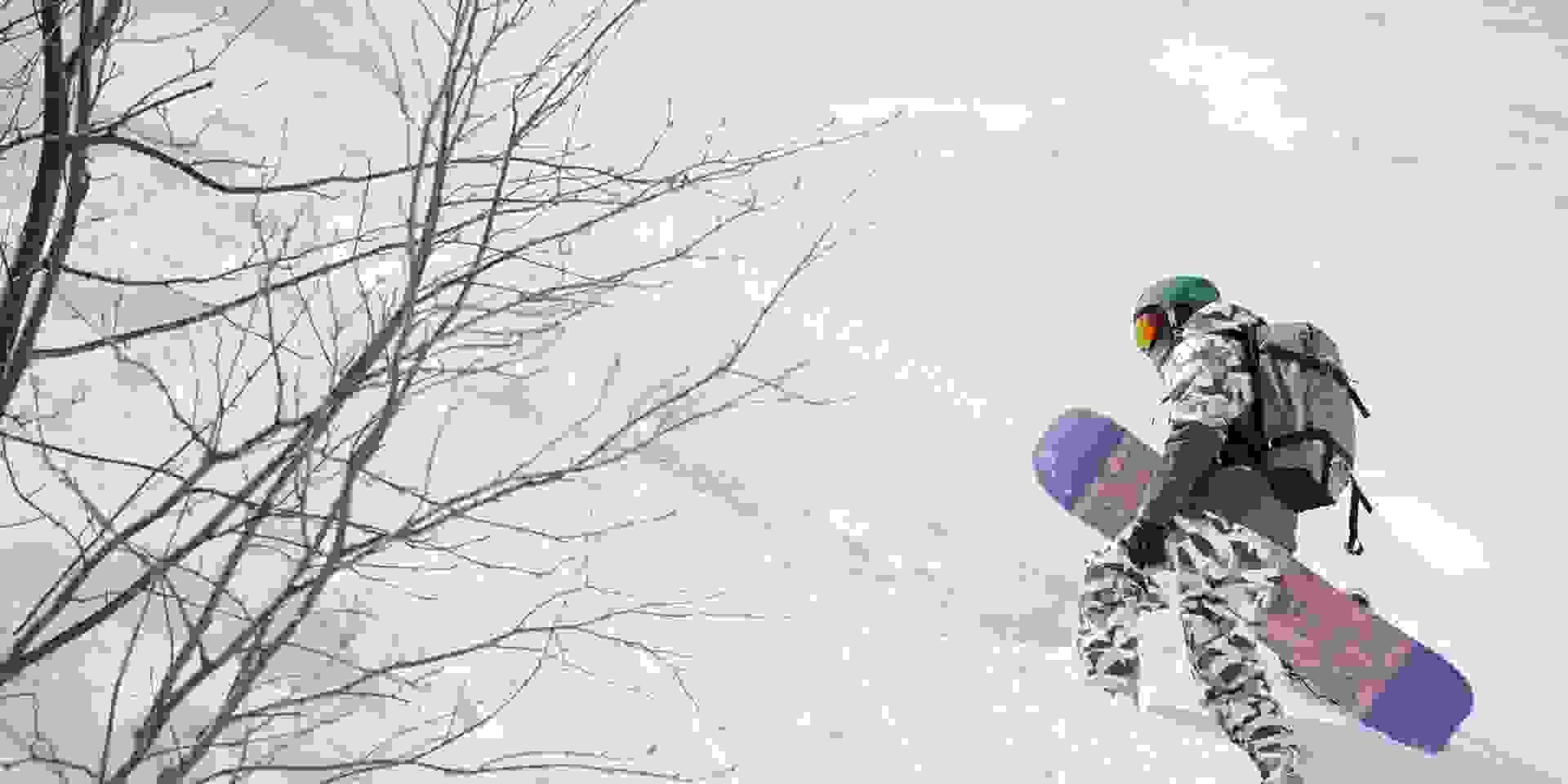 Ein Snowboarder steigt einen unberührten Tiefschneehang hinauf.