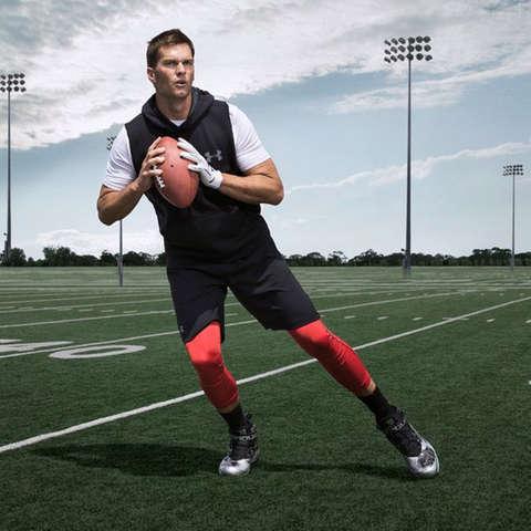 Tom Brady steht auf dem Football Feld und ist bereit zum Pass