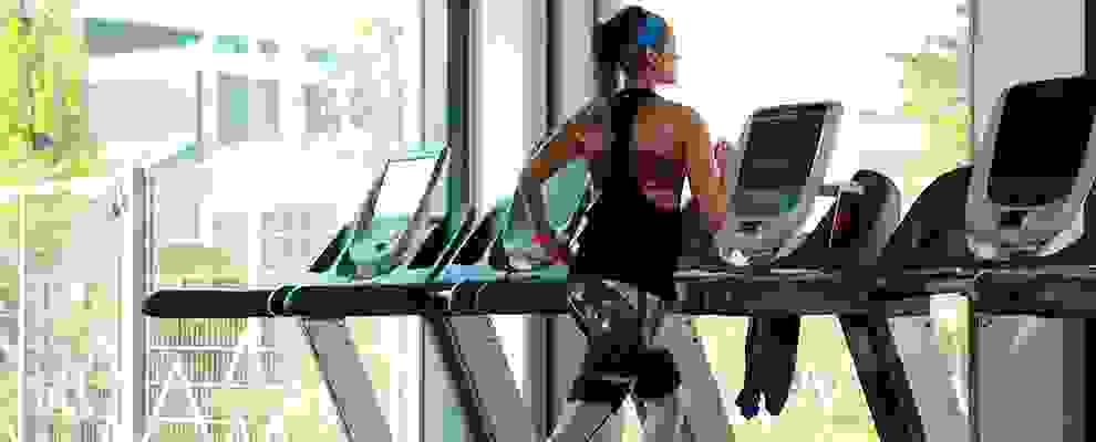 Eine Frau beim Ausdauertraining in einem Fitnessstudio. Sie läuft auf einem Laufband.