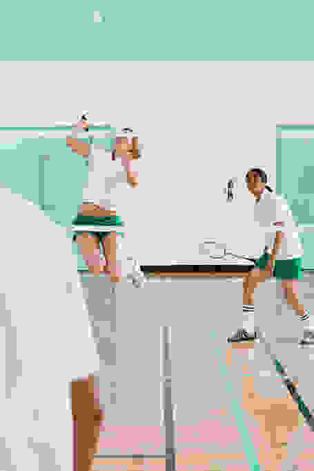 Eine Frau springt während des Badminton Spiels in die Luft, um an den Ball zu gelangen.