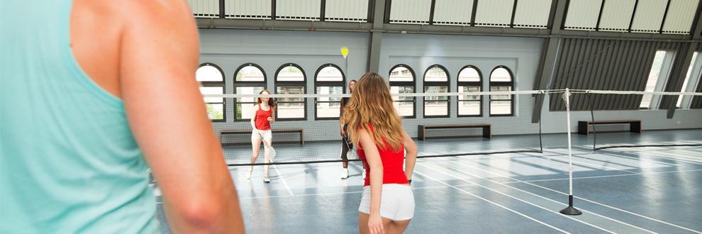 Eine Gruppe von Leuten spielt Badminton in der Halle.
