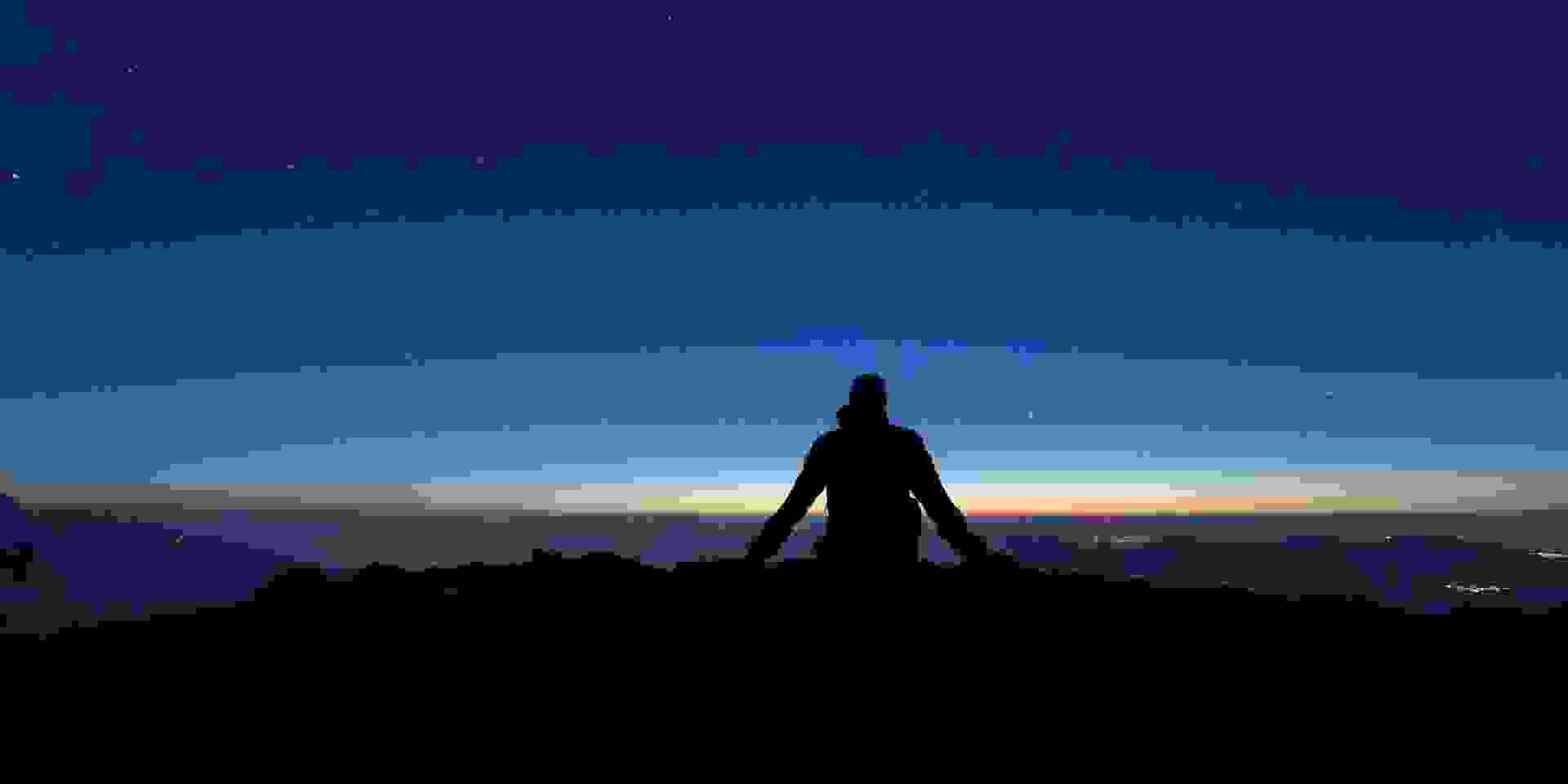 Ein Wanderer Blickt auf ein nächtliches Bergpanorama.