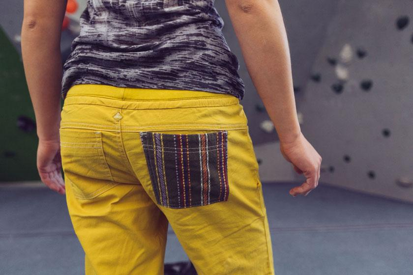 Die Rückseite einer gelben Boulderhose mit farblich abgesetzter Gesäßtasche.