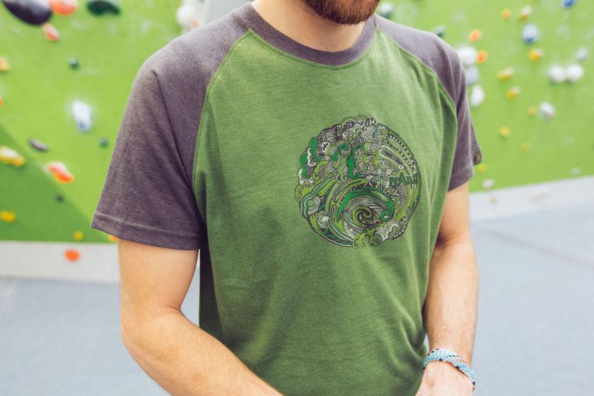 Ein grünes Bouldershirt mit buntem Fantasieaufdruck in der Nahaufnahme.