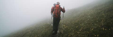 Ein Mann mit langen Haaren wandert mit Wanderstöcken in einem Gebirge.