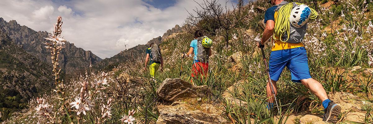 Zwei Männer und eine Frau wandern in kurzen Wanderhosen durch ein Gebirge.