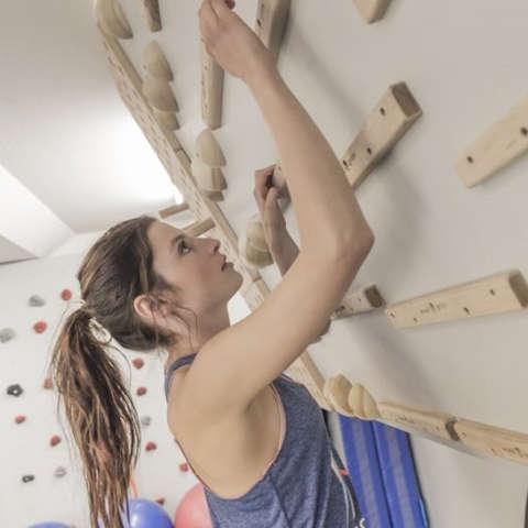 Eine Frau trainiert an einem Campus Board fürs Bouldern