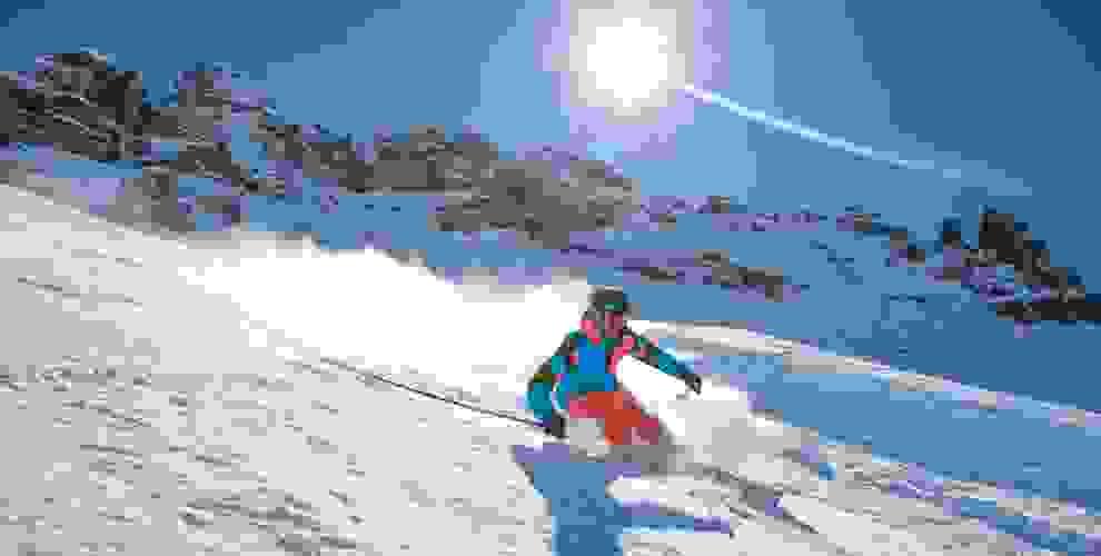Ein Skifahrer ist im Pulverschnee auf Carving Skiern unterwegs.