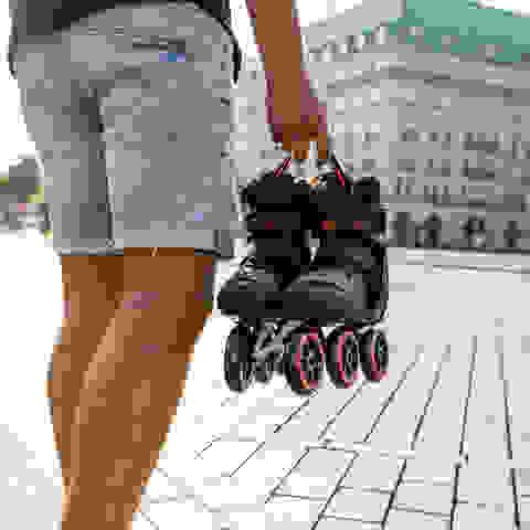 Ein Mann trägt ein paar Inline Skates in der Hand