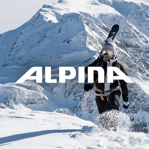 Ein Mann und eine Frau stehen vor einem Bergpanorama. Sie tragen beide verspiegelte Alpina Skibrillen und Skihelme.