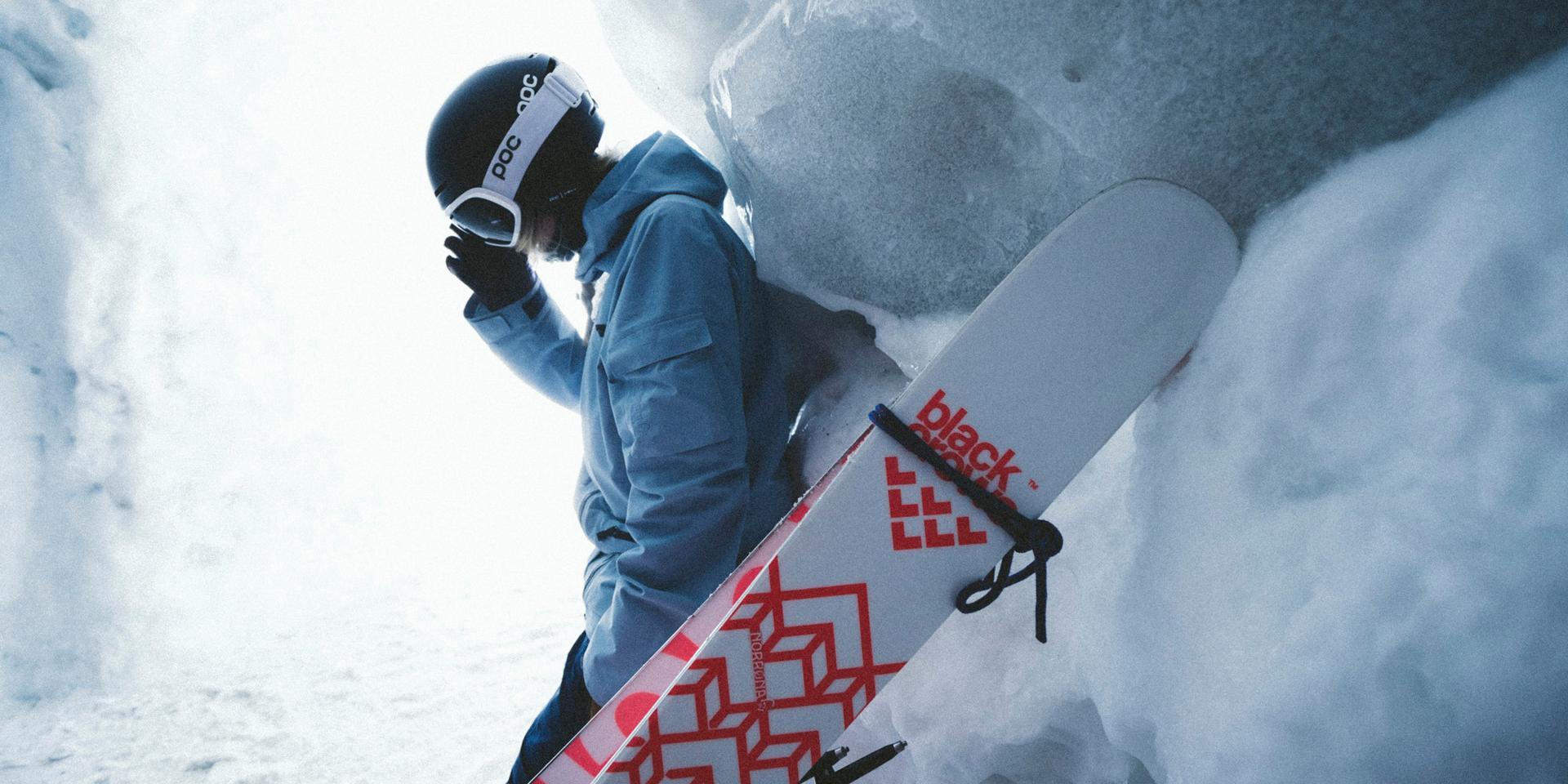 Eine Skitourengeherin lehnt hinter ihren passenden Tourenskiern auf einem Berg.