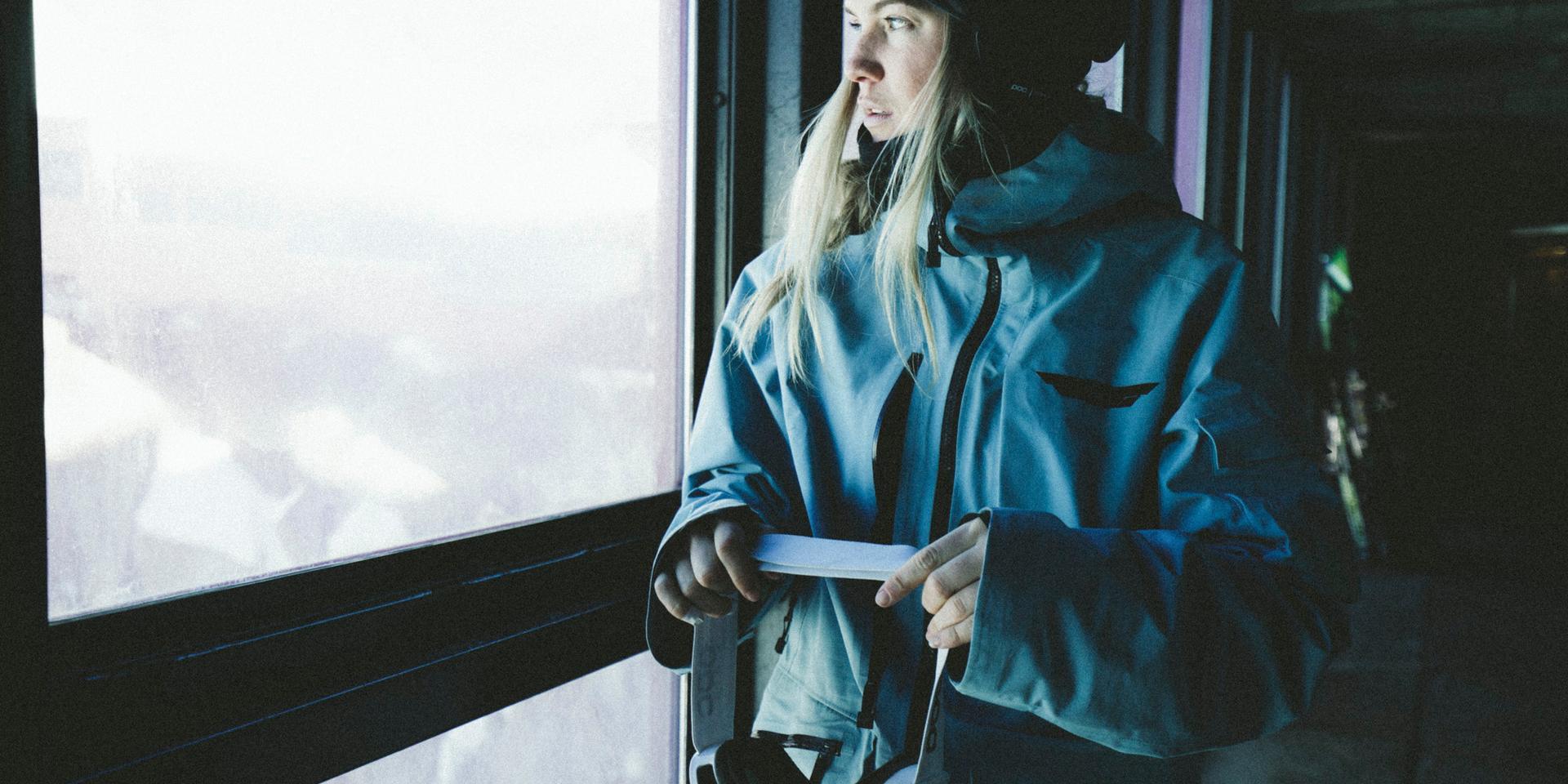 Eine Frau in voller Skitourenbekleidung in einer Hütte kurz vor der Abfahrt