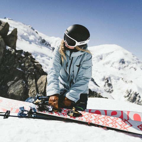Eine Skitourerin kniet auf dem Berg hinter ihrer nützlichen Skitouren Ausrüstung bereit zur Abfahrt.