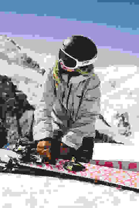 Ein Skifahrer legt der Länge nach an seinem Tourenski ein Skifell an.