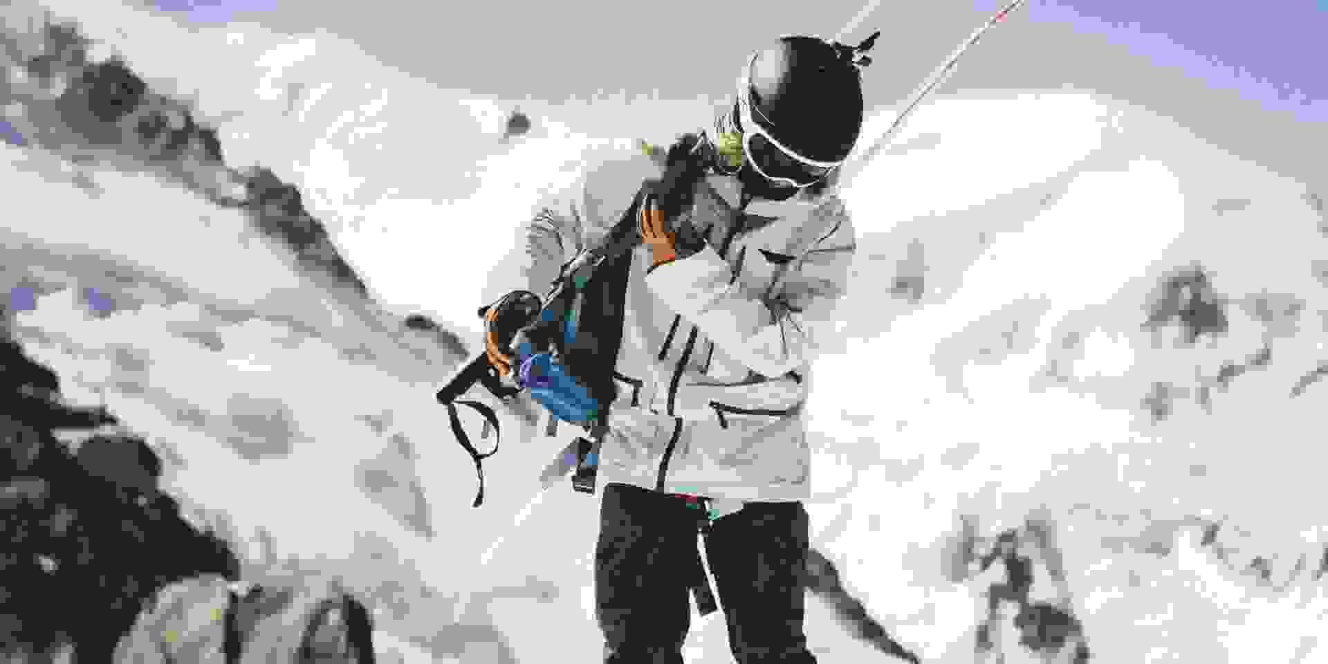 Eine Skitourengeherin setzt sich den Rucksack auf.