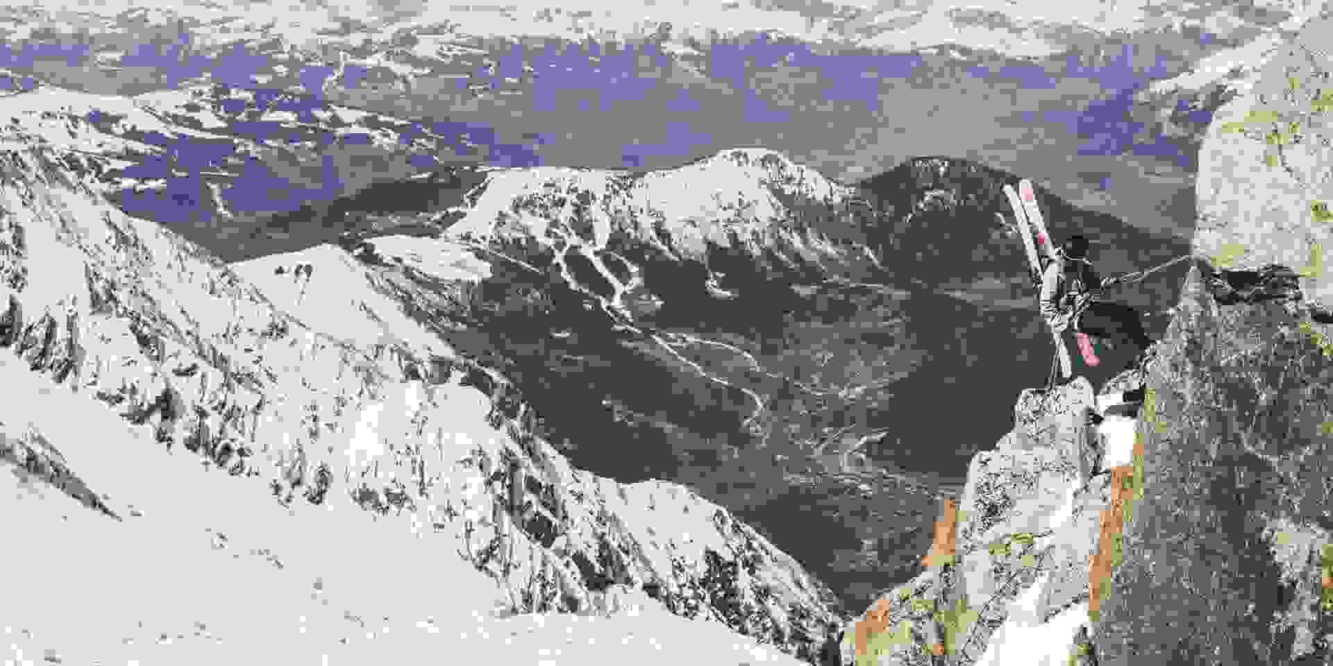 Eine Bergkette, auf der sich eine Skitourengeherin abseilt.