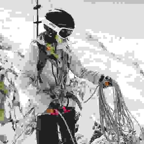 Eine Skitourerin die voll ausgerüstet ist. Sie tragt Skier, Rucksack,Helm. Seil und vieles mehr.