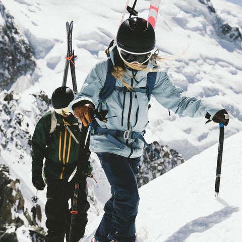 Eine Frau prüft ihren Tourenski. Im Hintergrund steht ein Mann und zieht ein Steigfell auf seinen Tourenski.