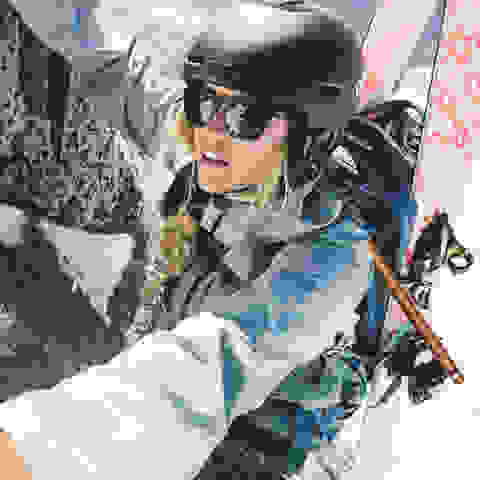 Ein Frau klettert mit einem Helm einen Berg hoch mit ihrer Skiouren Hardware auf dem Rücken.
