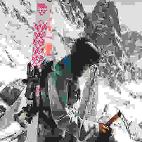 Eine Skitourerin hat ihre Tourenski auf den Rücken geschnallt