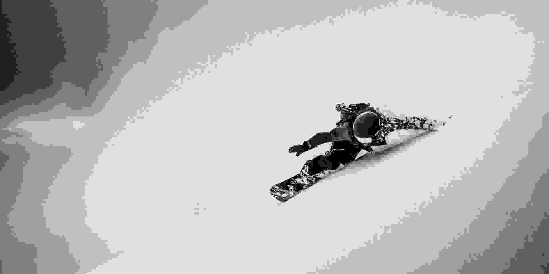 Ein Snowboarder fährt eine Piste hinab. Sein Fahrniveau ist sehr hoch.