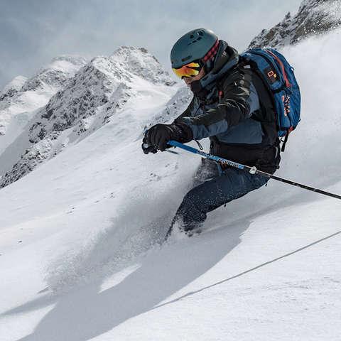 Ein Freeride Skifahrer fährt mit seinen Freeride Ski einen Hang im Tiefschnee hinab