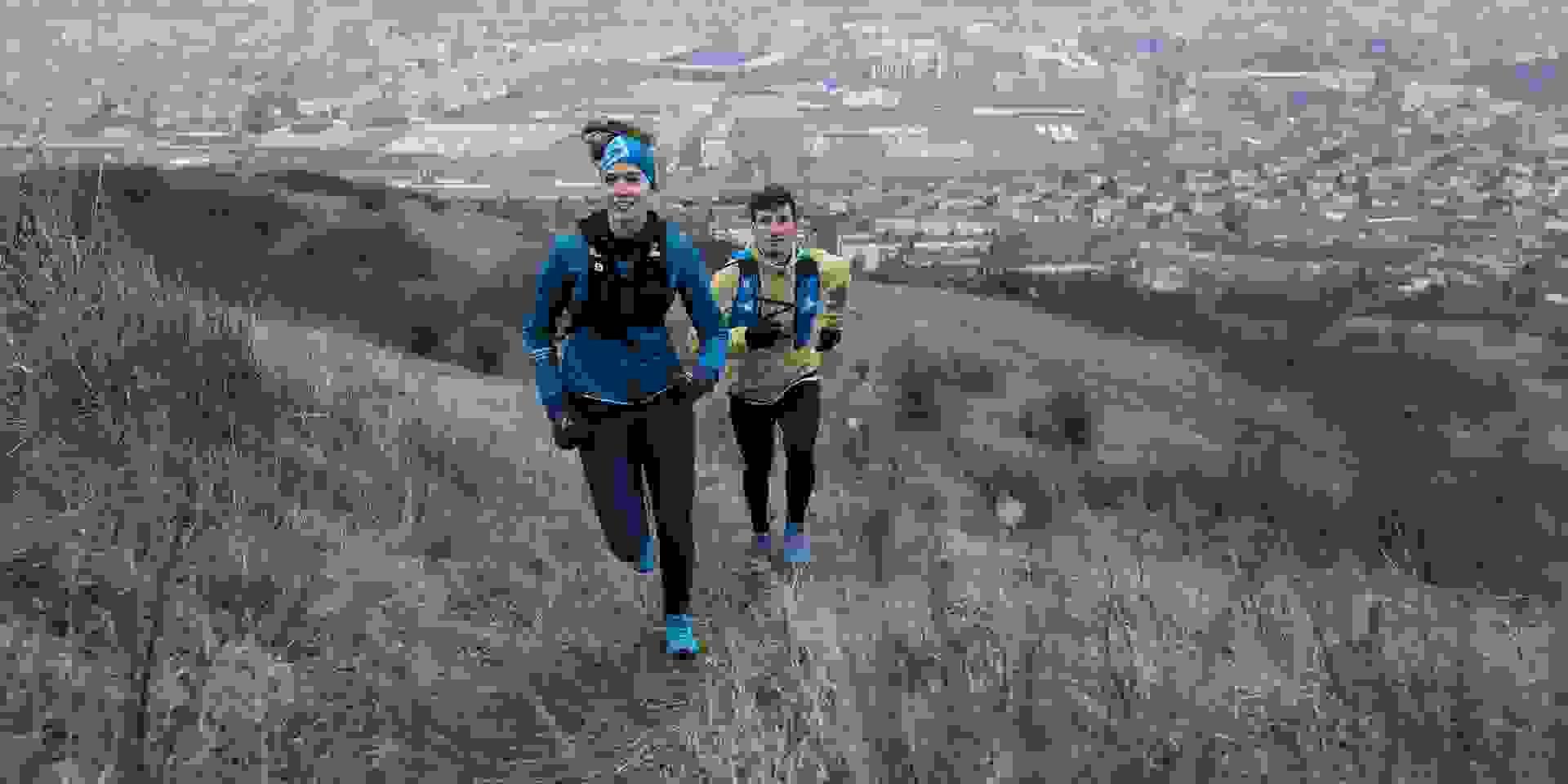 Zwei Trailrunner laufen einen Trail am Rande einer Stadt.