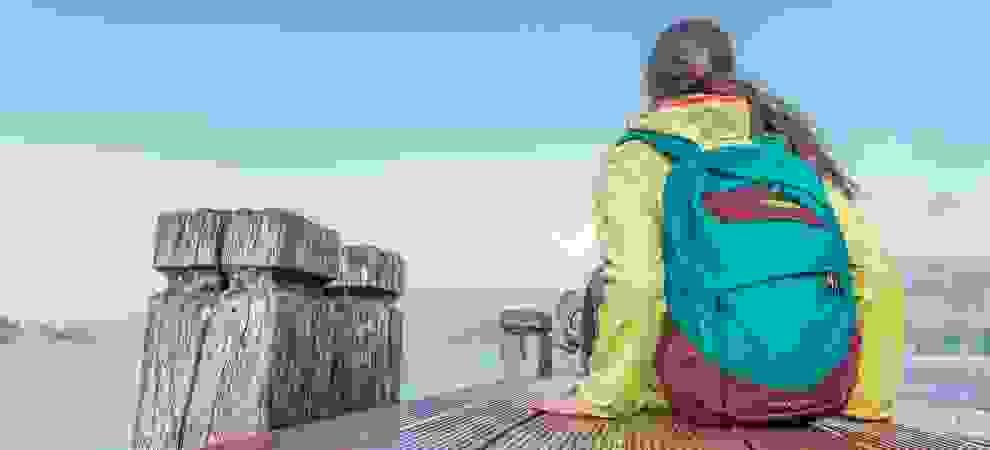 Eine Frau sitzt auf einem Bootssteg und trägt ein Daypack auf ihrem Rücken.