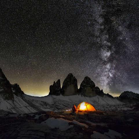 Ein Zelt steht in der Nacht vor den Drei Zinnen in den Dolomiten.