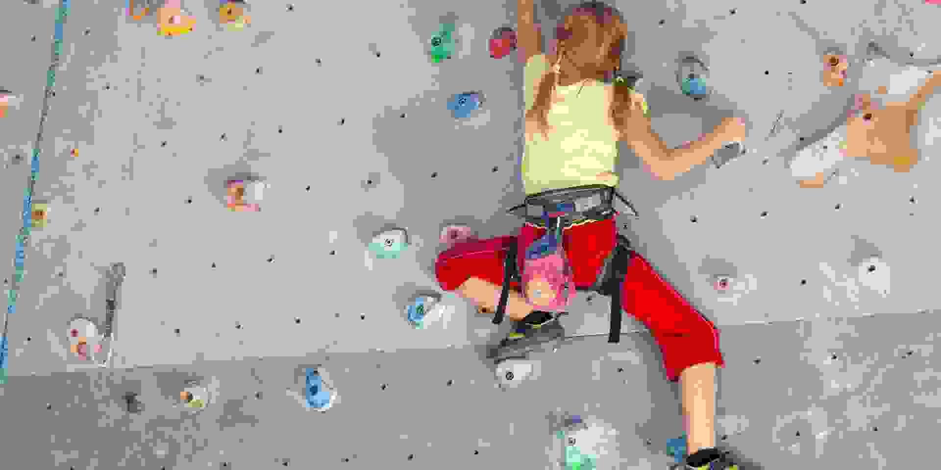 Ein Mädchen klettert Toprope in der Halle