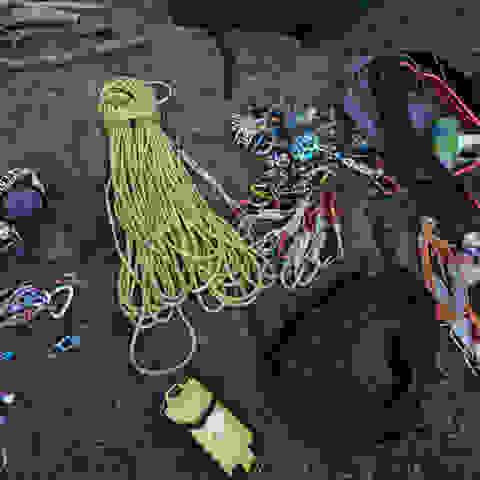 Diverse Kletterausrüstung auf dem Fußboden ausgebreitet.