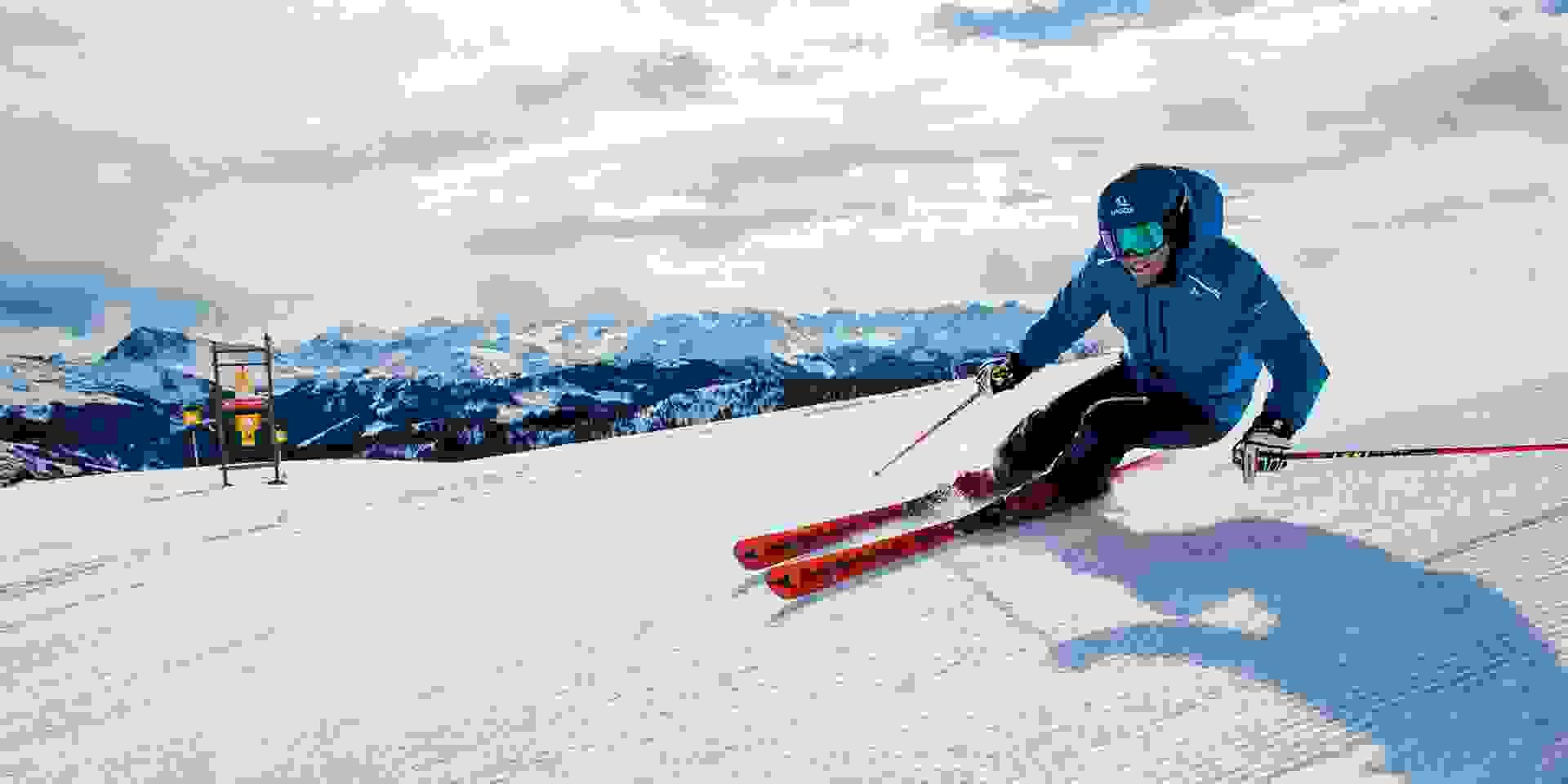 Ein Skifahrer fährt sehr schnell eine perfekt präparierte Piste hinab.