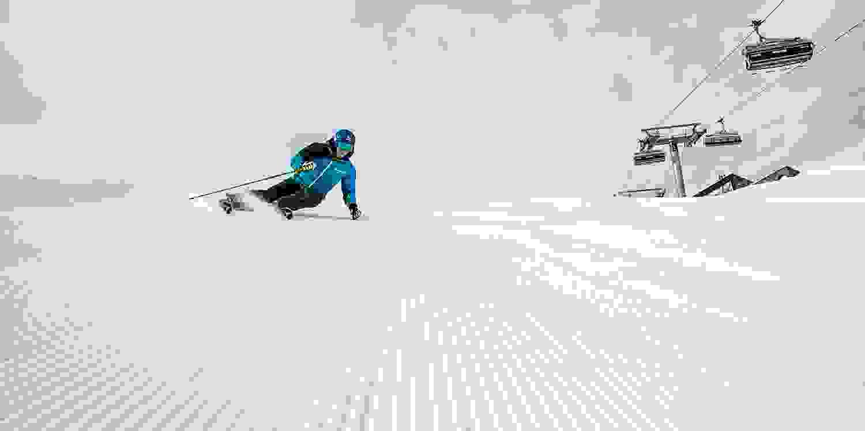 Ein Skifahrer fährt sehr schnell eine präparierte Piste hinab.