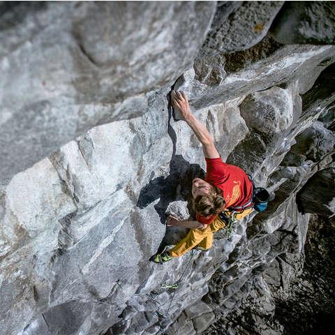Ein Mann klettert an einer Felswand ohne Sicherung hinauf.