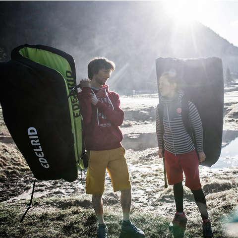 Zwei Kletterer unterhalten sich während sie Crashpads auf dem Rücken tragen