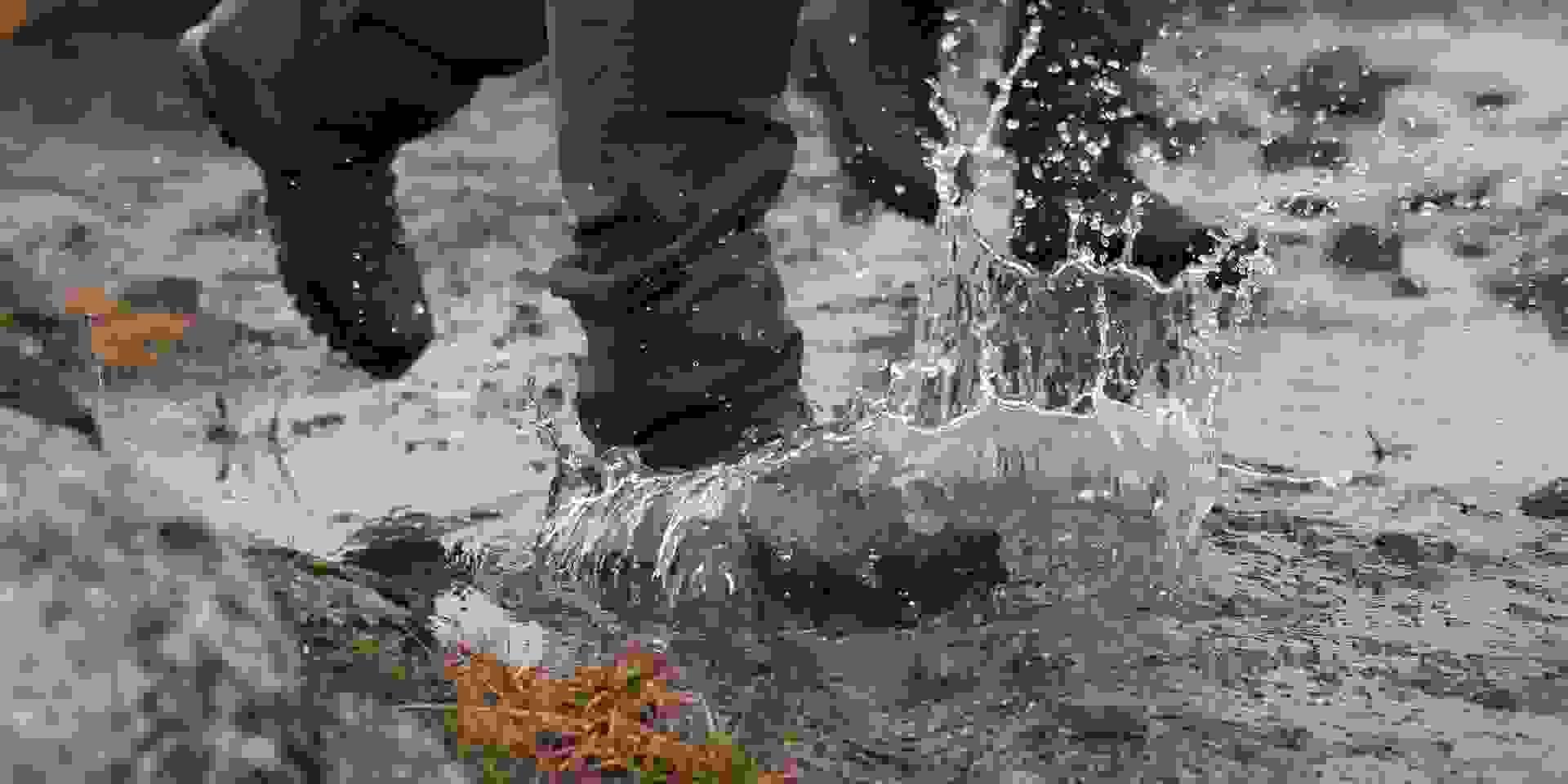Eine Aufnahme von Füßen die mit Wanderschuhen und Wanderhosen durch ein Flussbett wandern