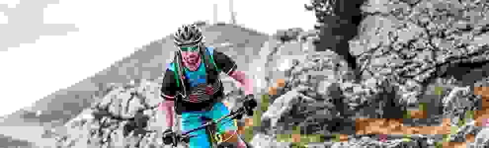 Ein Mann fährt mit seinem Mountainbike im Gelände. Auf dem Rücken trägt er einen Fahrradrucksack.