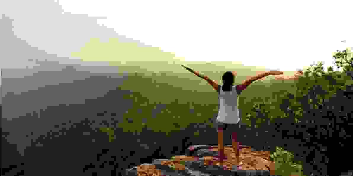 Eine Frau steht auf einem Berg bei Sonnenuntergang.