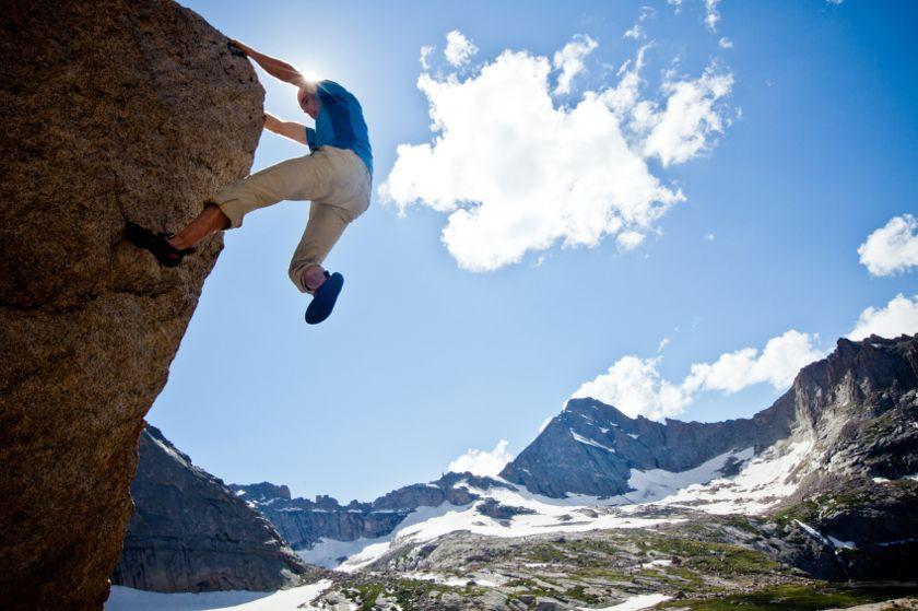 Ein Freeclimber hängt an einem Felsvorsprung. Im Hintergrund ein Blauer Himmel mit weißen Wolken.