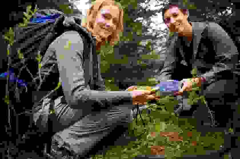 Ein junger Mann und eine junge Frau beim Geocaching. Sie halten einen Cache in der Hand.