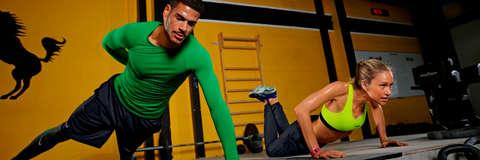 Ein Mann macht in einem Fitnessstudio einarmige Liegestütze und zeichnet sein Training mit einem Fitnesstracker auf.
