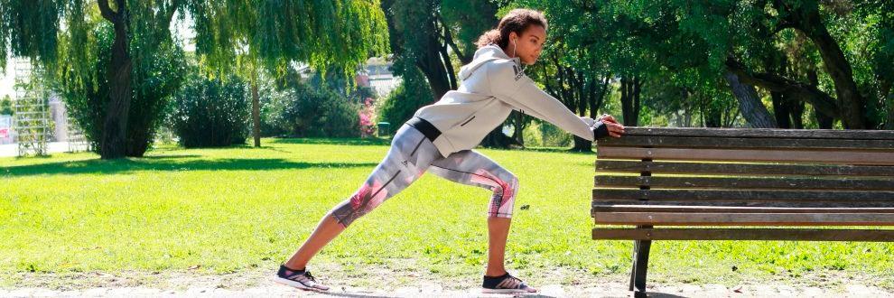 Eine Frau wärmt sich für Ihr Training im Park an einer Bank auf.