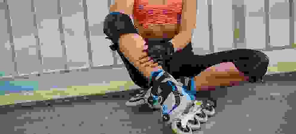 Eine Frau sitzt auf dem Boden und lehnt mit dem Rücken an einem Geländer. An den Füßen trägt sie Fitness-Skates.