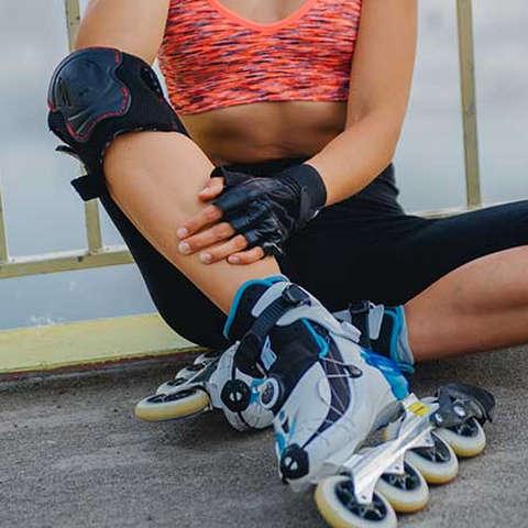 Eine Frau mit Inline Skates sitzt auf dem Boden